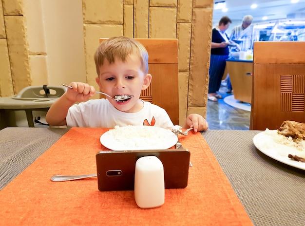 Porträt eines kleinen jungen, der beim essen im restaurant oder café cartoons auf dem smartphone sieht