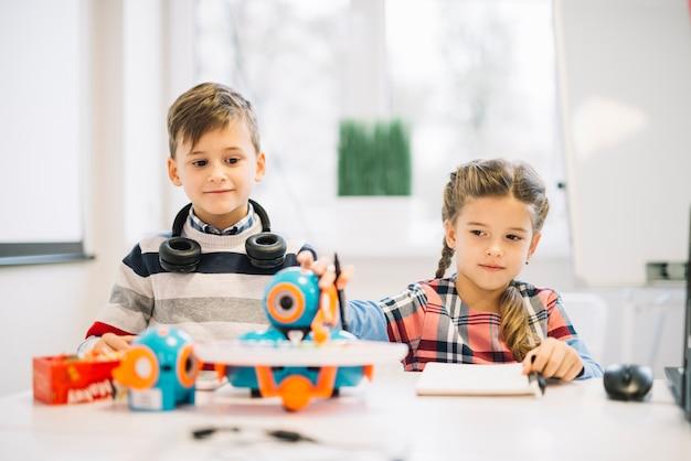 Porträt eines kleinen jungen, der das mädchen spielt mit roboterspielzeug betrachtet