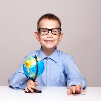 Porträt eines kleinen jungen, der eine kugel anhält. reisekonzept