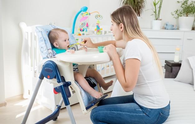 Porträt eines kleinen jungen, der im hochstuhl sitzt und brei isst