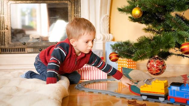 Porträt eines kleinen jungen, der im wohnzimmer auf dem boden sitzt und spielzeugeisenbahn auf eisenbahnen unter dem weihnachtsbaum betrachtet