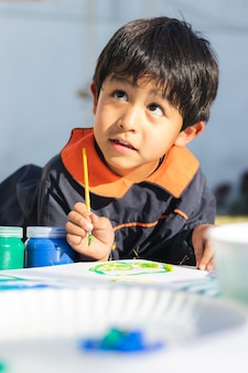 Porträt eines kleinen jungen, der mit einem pinsel auf einer weißen oberfläche malt, einen kittel trägt, im hof an einem sonnigen tag
