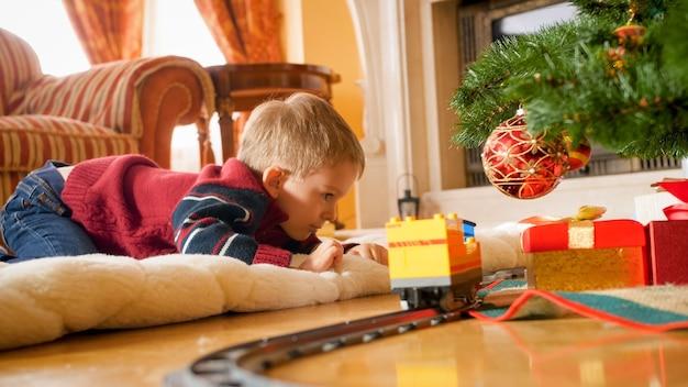 Porträt eines kleinen jungen, der mit einer spielzeugeisenbahn spielt, die er zu weihnachten vom weihnachtsmann bekommen hat. kind erhält geschenke und spielzeug an neujahr oder weihnachten