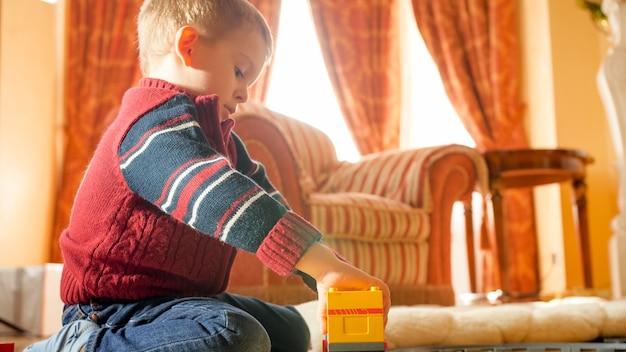 Porträt eines kleinen jungen, der mit spielzeug auf holzboden im wohnzimmer gegen großes fenster spielt