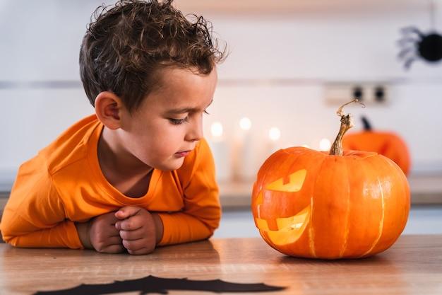 Porträt eines kleinen jungen, der seinen kürbis betrachtet, der für den feiertag von halloween dekoriert und beleuchtet ist...