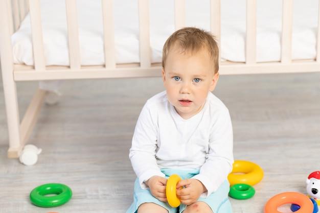 Porträt eines kleinen jungen, der zwei jahre alt ist und in der nähe der krippe spielt