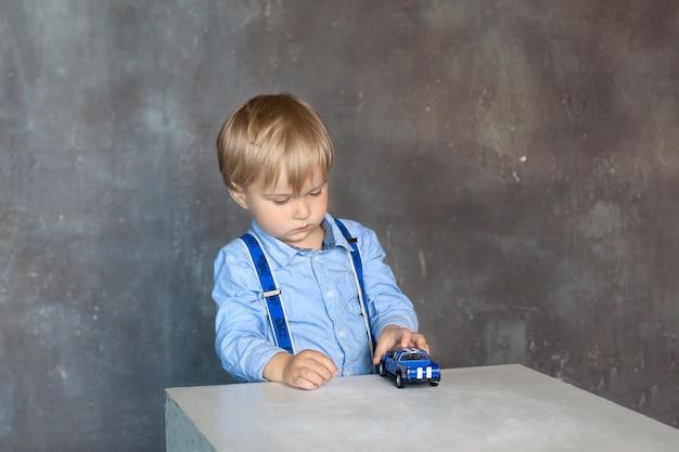 Porträt eines kleinen jungen in einem hemd mit hosenträgern spielt mit mehrfarbigen spielzeugautos des spielzeugs zu hause. ein junge spielt mit einem spielzeugauto auf einem tisch im kindergarten. das konzept der kindheit und der kindlichen entwicklung