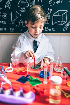 Porträt eines kleinen jungen wissenschaftlers, der bunte chemische flüssigkeiten gegen die tafel mit zeichnungen mischt