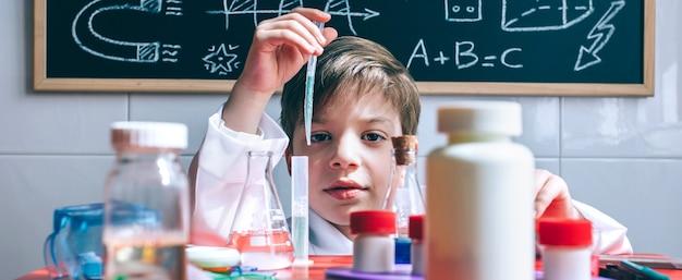Porträt eines kleinen jungen wissenschaftlers, der flüssigkeit aus dem reagenzglas hinter dem tisch mit chemischem spielzeug extrahiert