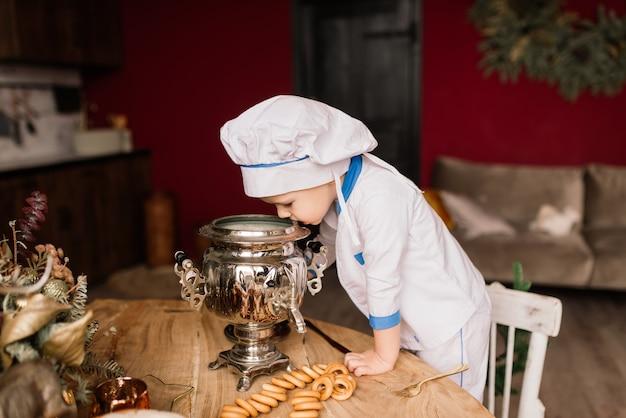 Porträt eines kleinen jungenkochs, der pfanne an der küche hält. verschiedene berufe. isoliert über weißem hintergrund. zwillingsbrüder