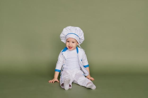 Porträt eines kleinen jungenkochs, der pfanne an der küche hält