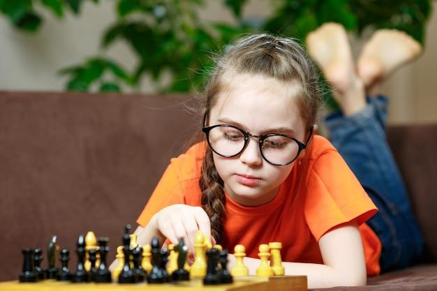 Porträt eines kleinen kaukasischen mädchens mit brille, die zu hause während der quarantäne wegen coronavirus schach spielt.