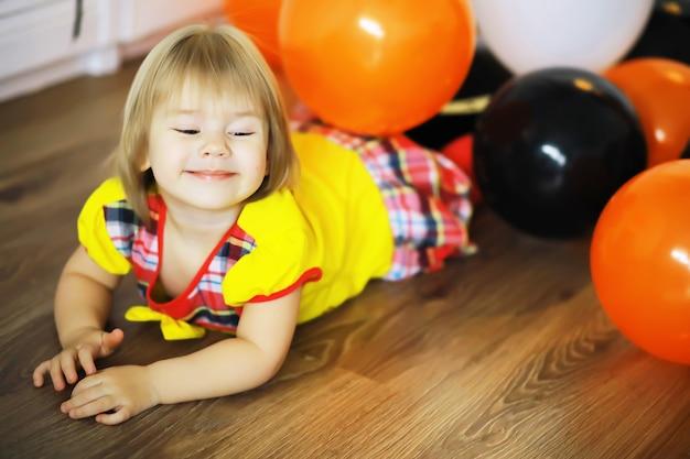 Porträt eines kleinen kindes, das in einem mit luftballons geschmückten raum auf dem boden liegt. glückliches kindheitskonzept.