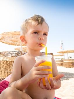 Porträt eines kleinen kleinkindjungen, der auf der sonnenliege am meeresstrand sitzt und orangensaft aus stroh trinkt