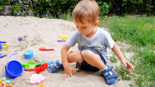 Porträt eines kleinen kleinkindjungen, der mit spielzeug spielt und sand im sandkasten im park gräbt?