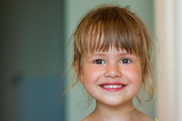 Porträt eines kleinen lächelnden mädchens auf unscharfem hintergrund