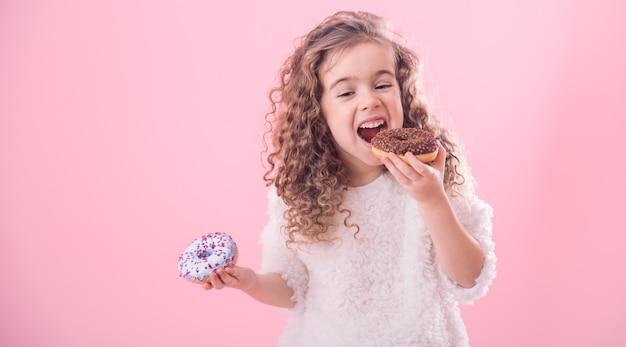 Porträt eines kleinen lockigen mädchens, das donuts isst