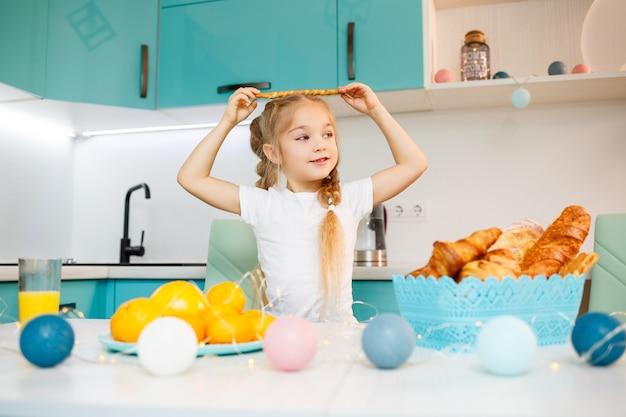 Porträt eines kleinen mädchens 7 jahre alt sitzt in der küche und spielt mit brotstangen. kind frühstückt in der küche