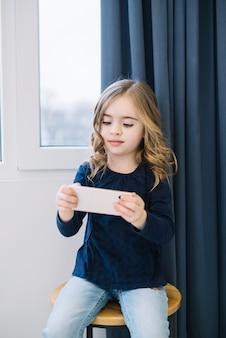 Porträt eines kleinen mädchens, das auf dem schemel betrachtet intelligentes telefon sitzt
