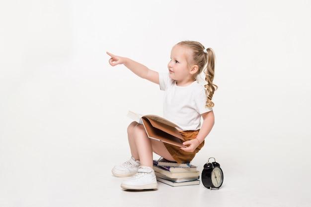 Porträt eines kleinen mädchens, das auf einem stapel bücher sitzt.