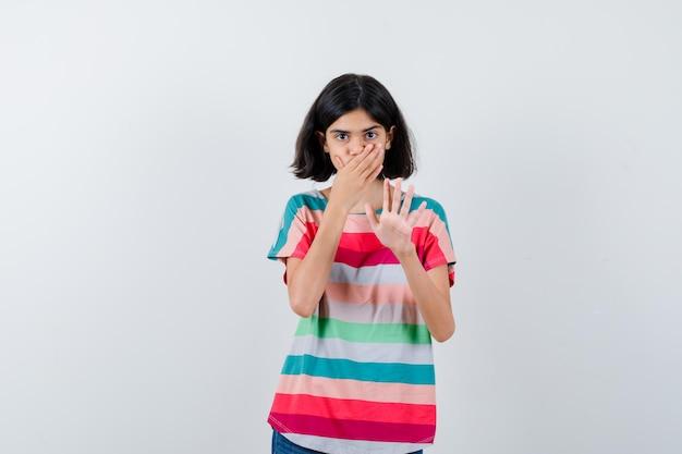 Porträt eines kleinen mädchens, das die hand auf den mund hält, eine stopp-geste im t-shirt zeigt und verängstigte vorderansicht sieht