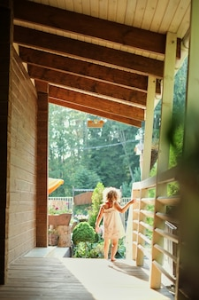 Porträt eines kleinen mädchens, das draußen entlang der veranda geht,