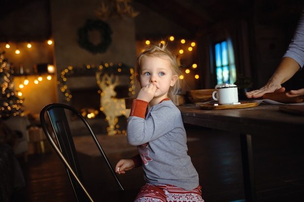 Porträt eines kleinen mädchens, das eibisch isst, während ihre großmutter traditionelle plätzchen zubereitet. konzept gemütliche weihnachten.