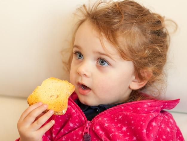 Porträt eines kleinen mädchens, das einen zwieback isst