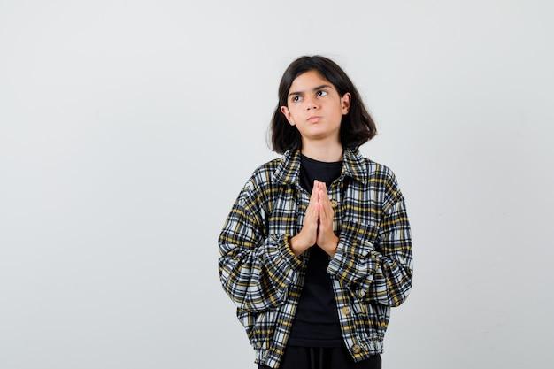 Porträt eines kleinen mädchens, das gefaltete hände in flehender geste in t-shirt, jacke und hoffnungsvoller vorderansicht zeigt