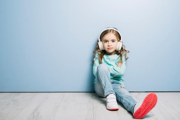 Porträt eines kleinen mädchens, das gegen blau mit kopfhörer auf ihrer hörenden kopfmusik sitzt