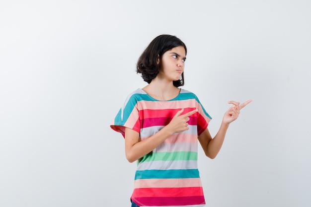 Porträt eines kleinen mädchens, das im t-shirt auf die rechte seite zeigt und zweifelhafte vorderansicht sieht