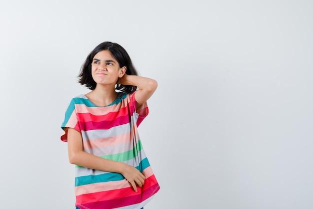 Porträt eines kleinen mädchens, das im t-shirt die hand am hals hält und hoffnungslose vorderansicht sieht