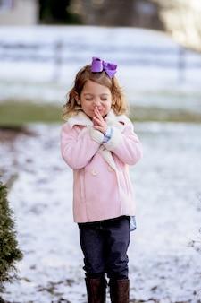 Porträt eines kleinen mädchens, das in einem park betet, der im schnee unter dem sonnenlicht bedeckt ist