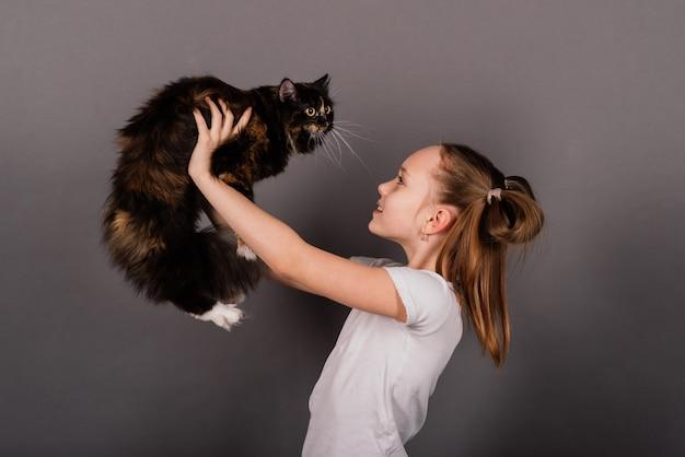 Porträt eines kleinen mädchens, das mit ihrem haustier spielt, schwarze große katze