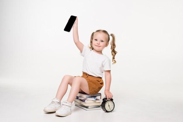 Porträt eines kleinen mädchens, das telefonbildschirm hält, der auf einem stapel bücher sitzt.