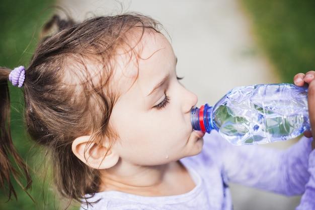 Porträt eines kleinen mädchens, eines mädchens, das wasser aus einer plastikflasche trinkt, regen, nasses haar, im sommer mit ihrer mutter spazierend, pferdeschwänze auf dem kopf, lächeln, plastik