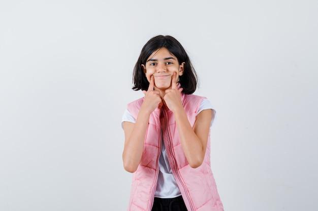 Porträt eines kleinen mädchens im weißen t-shirt und in der pufferweste, die ein lächeln erzwingen