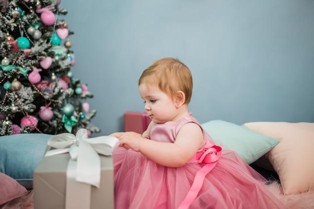 Porträt eines kleinen mädchens in einem festlichen rosa kleid, das ein geschenk auf dem hintergrund eines weihnachtsbaumes öffnet