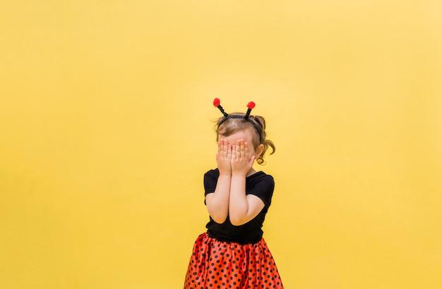 Porträt eines kleinen mädchens in einem marienkäferkostüm schloss ihre augen auf einem gelben isolierten