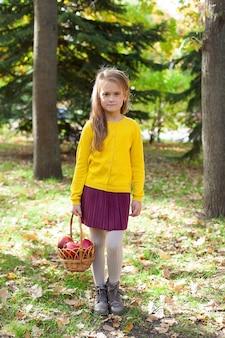 Porträt eines kleinen mädchens in einem park mit einem granatapfel. umarmungen und lächeln.