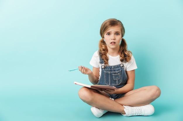 Porträt eines kleinen mädchens isoliert über blauer wand, in ein notizbuch schreibend