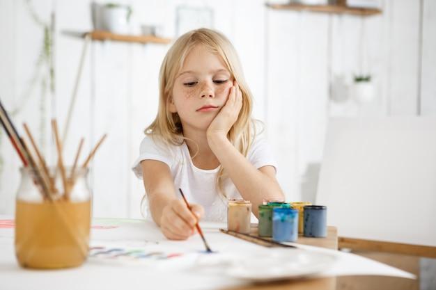 Porträt eines kleinen mädchens mit blonden haaren und sommersprossen, das am schreibtisch sitzt und ihren ellbogen auf den tisch legt
