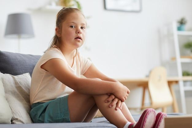 Porträt eines kleinen mädchens mit down-syndrom beim ausruhen auf dem sofa im wohnzimmer