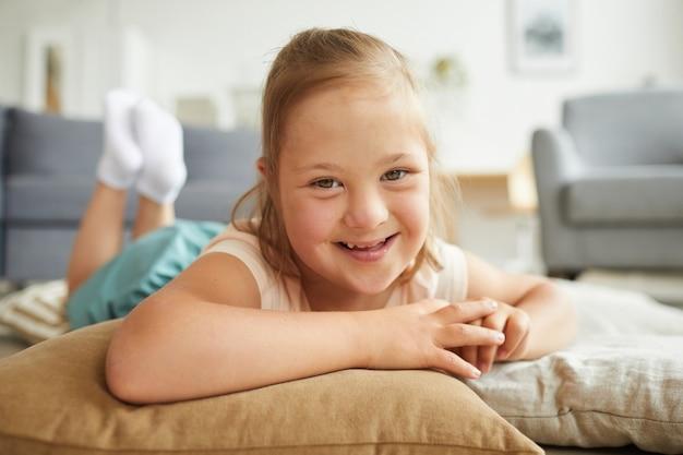 Porträt eines kleinen mädchens mit down-syndrom, das in die kamera lächelt, während es auf kissen auf dem boden liegt