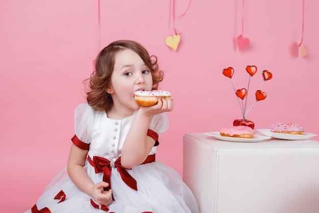 Porträt eines kleinen mädchens mit einem donut in ihren händen auf rosa