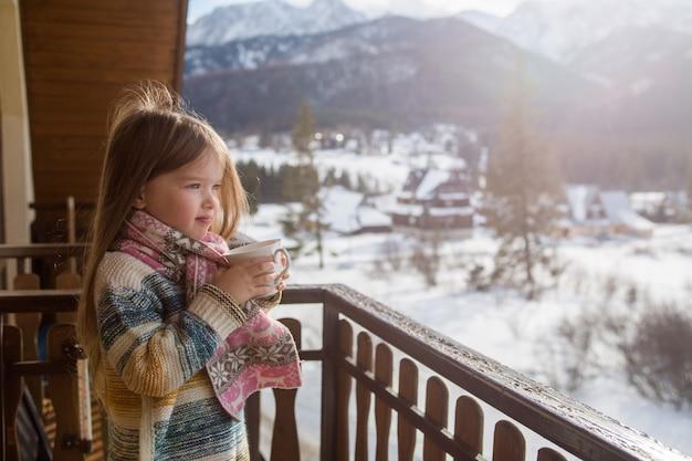 Porträt eines kleinen mädchens mit einer tasse tee auf bergen, zakopane, koscielisko.