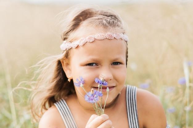 Porträt eines kleinen mädchens mit kornblumen. sommerurlaub konzept.