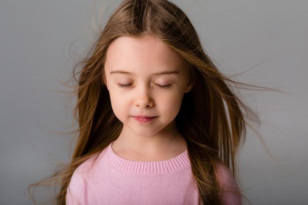 Porträt eines kleinen mädchens mit langen haaren auf einem hellen raum