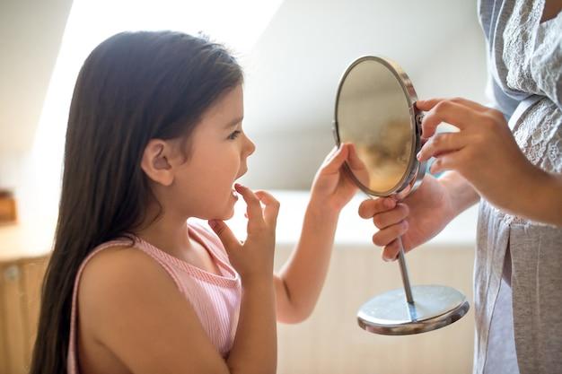 Porträt eines kleinen mädchens mit mutter im badezimmer drinnen, im spiegel auf den losen zahn des babys schauend.