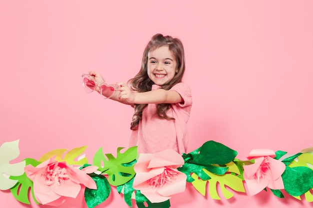 Porträt eines kleinen mädchens mit sonnenbrille auf einem rosa hintergrund